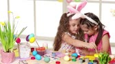 decorative rabbit : Happy children wearing bunny ears painting eggs on Easter day. two little girls preparing for the Easter. Stock Footage