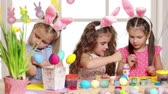 narcis : Happy children wearing bunny ears painting eggs on Easter day. Little girls preparing for the Easter.