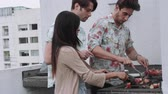 cardigan sweater : Men and woman having barbeque on rooftop terrace Stock Footage