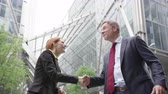 Businesswoman shaking hands with Businessman outdoors in the city Stock Footage