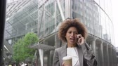 Afro American businesswoman in city using smart phone with takeaway coffee