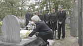 supporting : Senior woman laying flowers on grave