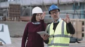 Construction workers discussing project development on site