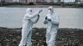 evidência : Forensic scientist taking sample at river bank