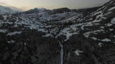 peaked : United States - Aerial Flying Towards Epic Waterfall, Mountain Lake, and Snowy Peaks at Sunset Stock Footage