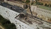 Description: Workers clean the roof of a multi-storey building from an old roofing felt. Repairing or re-roofing. Birds eye Aerial view. 4k video