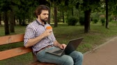 Bearded man is sitting at bench in park and working with laprop. He is typing and taking cup of coffee. Wideo