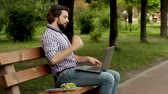 hambúrguer : Man is walking to bench and sitting on it. He puts folders and burger on bench. Man puts laptop on legs and open it.