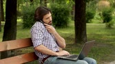 Busy man is sitting on bench and working on laptop and talking on the phone. Wideo