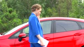 estacionamento : Business woman walks in front of car back and forth several times, talks on phone and holds paper notes in hand. Stock Footage