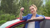 способ : Nice woman in bluse suit stands and leans to door. She holds keys from car. Стоковые видеозаписи