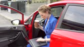 bom : Busy woman sits in car and works. holds laptop on nap and cup of coffee in hands.