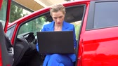 Girl sits in car with the doors opened. Drinks coffee from cup and look at screen of laptop. Wideo