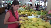 Girl choosing fresh fruit in the market. Mango close up