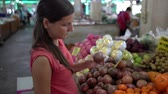 Girl choosing fresh fruit in the market