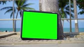 display : TV stands on the beach. Television with Green Screen. You can replace green screen with the footage or picture you want.