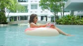 gonfiabili : Young female freelancer sitting with a laptop in an inflatable circle in the pool. Busy during the holidays. Remote work Concept. selective focus.