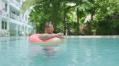 excesso de trabalho : Fat funny man in pink inflatable circle in pink glasses works on a laptop in a swimming pool.