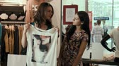 joy : Two girls try on shirts in shop Stock Footage