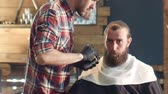 facial : Young barber cutting mans beard with trimmer