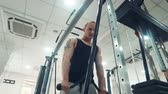 heavy : Handsome muscular man doing triceps exercise with rope in gym Stock Footage