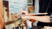 originality : Close up woman artist working in her studio with a closeup side view of the canvas on an easel and her hand mixing paints on a palette. Stock Footage