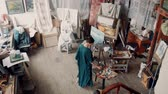 originality : Aerial view of a female artist wearing a smock standing in her studio painting a canvas on an easel surrounded by other covered canvasses and art supplies.