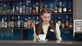 drink : Smiling waitress placing a coffee on the counter in a pub or bistro with shelves of alcoholic beverages behind her Stock Footage