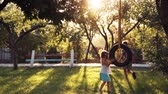 girl : Slow motion of happy girl and boy playing at park with tire swing hanging from tree with beautiful sunlight in background