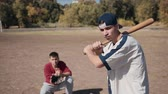 batedor : Slowmotion Young Male Batter Standing Ready for Pitch with Baseball Bat Over Shoulder During Casual Baseball Game in Sunny Field with Catcher Crouching in Background in Summer Time.