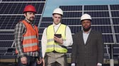 solar energy power : Trio of solar panel multi ethnic engineers and executive surrounded by large collector arrays outside looking camera Stock Footage