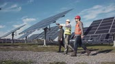 striding : Technician walks with workman and investor through field of solar panels