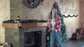 decorativo : Young woman weared in jeans and shirt designing fireplace for Christmas with snowman and candle toys, middle 4K shot Vídeos