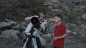 astrologia : Father sets up telescope for explore stars with son on rocky shore. Wideo