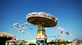 Fast time-lapse of the carousel swing ride at the carnival midway. Selective spot focus in center of image.-