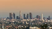 distante : Pull back zoom of Los Angeles downtown skyline at sunset. Hazy sky. Shot on 3CCD HD 1080. Circa 2007.- Stock Footage