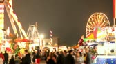 parkosított : People walking around at the carnival. Focus on the background, foreground defocused.-