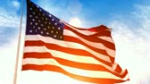 единение : Beautiful glowing footage of the American Flag flowing in the wind with a golden sunset in the background and a blue sky with white puffy clouds.- Стоковые видеозаписи