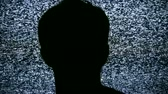 digitalmente : Silhouette of person watching static on HD 1080 TV. Seamless HD 1080 Loop. Shot on HDV 1080.- Stock Footage