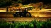 неузнаваемый : Silhouette shot of tractor plowing a field in the late afternoon. Shallow depth of focus on tractor.- Стоковые видеозаписи