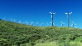 fornecimento : Spinning wind turbines on green hills and clear blue sky. Shot on HD 1080p. Stock Footage