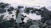 бросать : Cute girl sitting on the beach admiring the sunset and throwing pebbles into the sea 4k,30fps