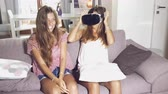 Two cute girls at home with VR glasses playing and having fun retro style