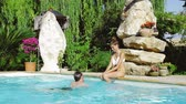 roupa de banho : Happy couple splashing in pool having fun with water Stock Footage