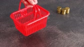 shopping budget and expenses concept, hand placing shopping basket next to stack of coins in the background (unfocused)