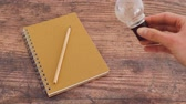 lightbulb metaphor of idea placed next to notebook with pencil on wooden desk