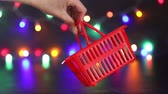 festive season shopping concept, hand swinging shopping basket in front of colorful Christmas string lights bokeh