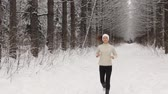 finding : Young woman listening to music and jogging outside in winter Stock Footage