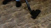 conservar : Man doing home cleaning. To vacuum vacuum cleaner floor laminate. To frame the feet in socks. 4K