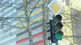 indicação : Traffic light switches from red to yellow and green on the background of a multi-storey building.